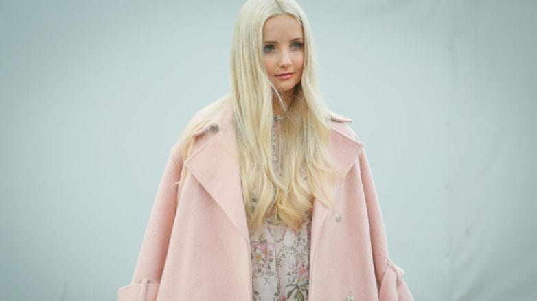 Purple shampoo: Blogger at fashion week with long light blonde blow-dried hair wearing a baby pink overcoat