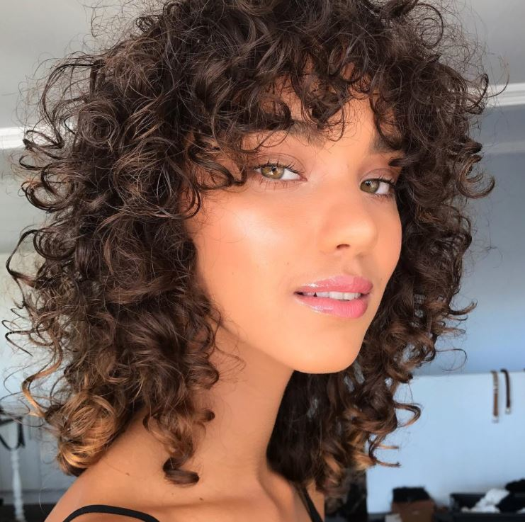 model with curly brown hair with very subtle blonde highlights at the tips