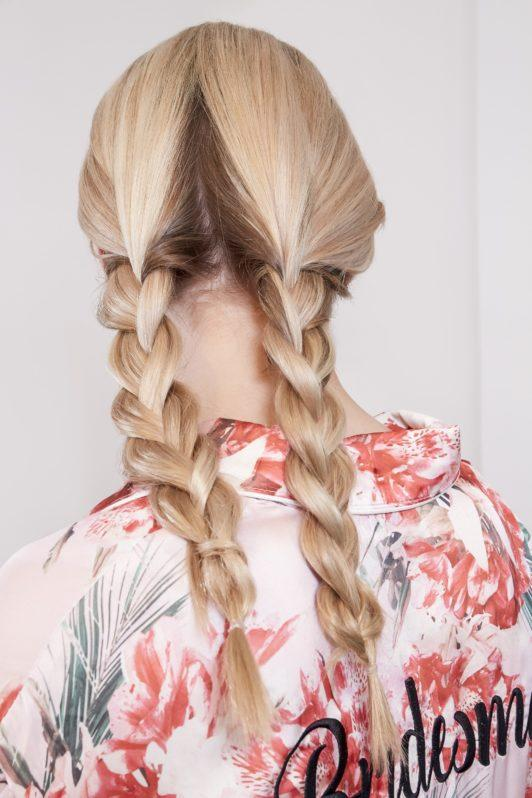 wedding chignon: blonde model with her hair in two pigtail braids wearing a floral bridesmaid robe