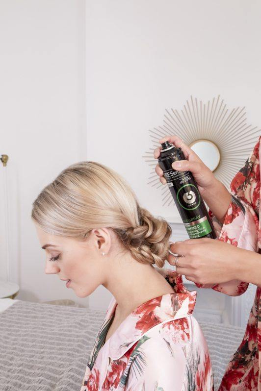 wedding chignon: blonde model with a braided wedding chignon having her hair sprayed with tresemme hairspray
