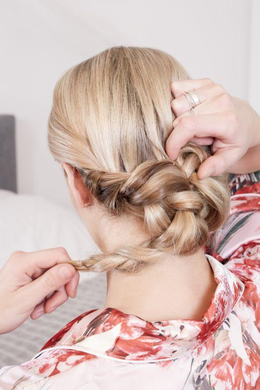 wedding chignon: back view of a blonde model wrapping her braided pigtails into a low chignon