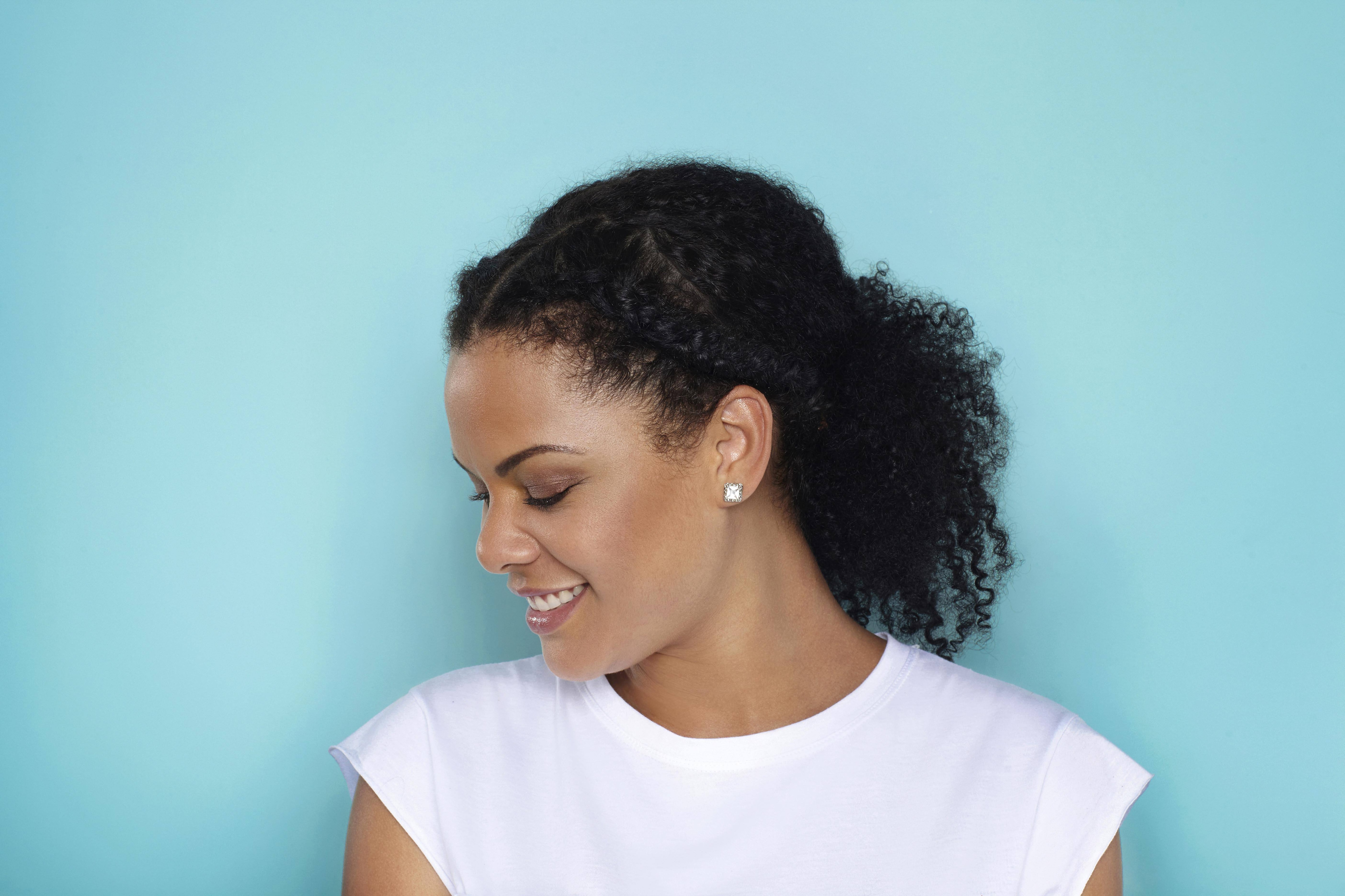 Curly hair hairstyles: side profile of woman with naturally curly hair in ponytail with braids at the front of the hair standing against a light blue backdrop wearing a white tshirt.