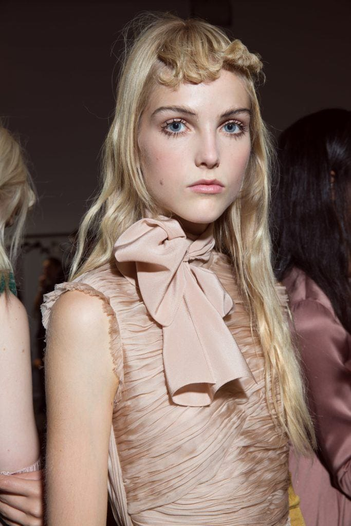 blonde model backstage at Rochas SS17 paris fashion week show wearing a dusty pink dress with a bow with long wavy hair with a curly fringe
