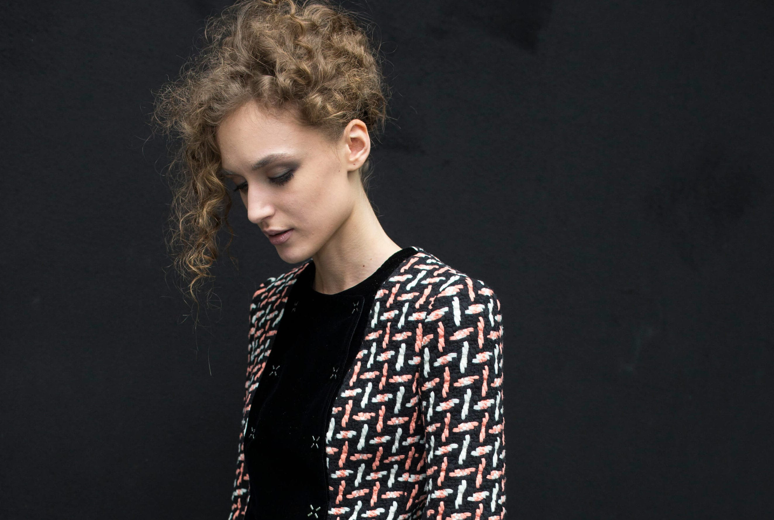 Curly hair hairstyles: woman with curly hair swept up in '80s style standing against a black backdrop wearing pattern jacket