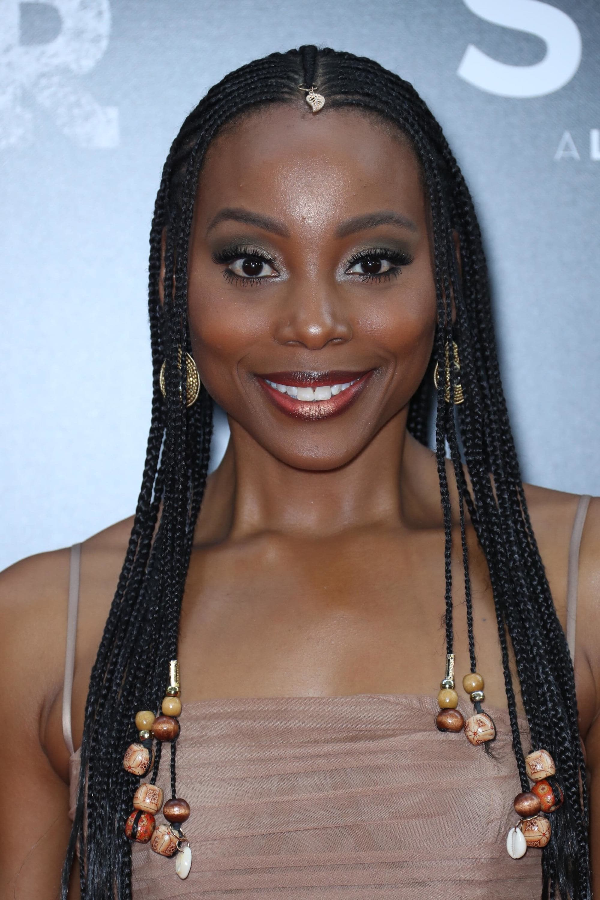 Black history month hairstyles: Close up shot of Erica Ash with dark brown cornrows with beads on the ends, wearing a brown top and posing on the red carpet