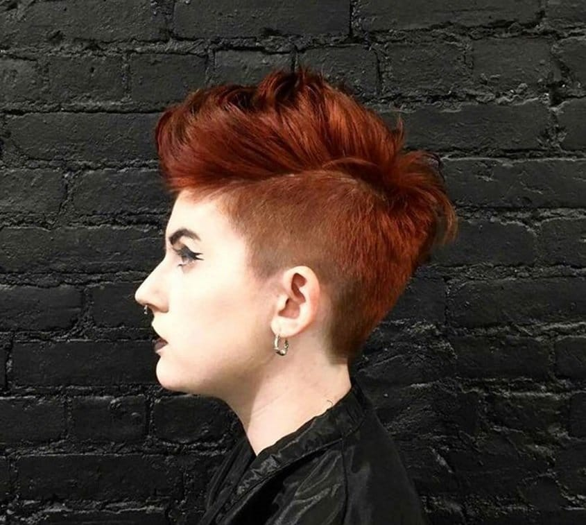 side view of a woman with dyed red hair in a shaved sides mohawk