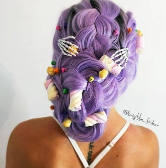 back shot of a woman with purple hair in a braid and halloween accessories attached
