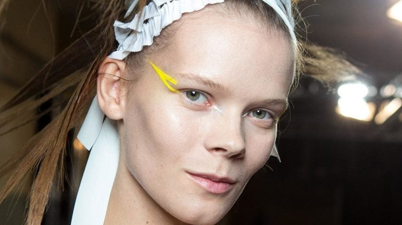 model backstage at the Haider Ackermann SS17 show with extreme spiky hair with a bandage wrapped around her head with a wing of colourful eyeliner