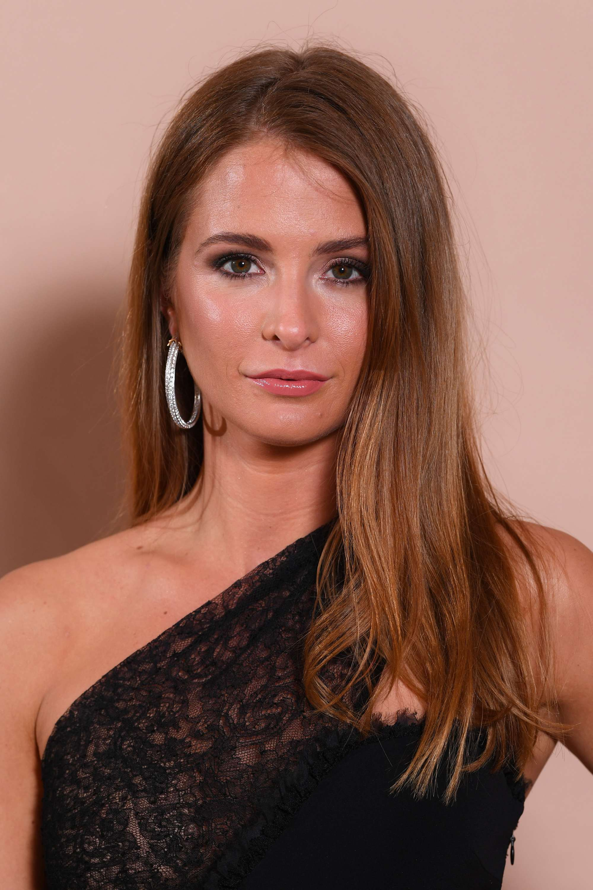 Millie Mackintosh with long layered caramel brown hair styled the side, wearing hoop earring with black dress on the red carpet