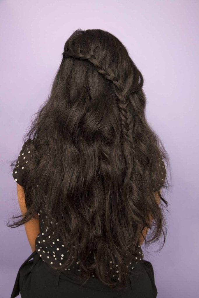 Divali hairstyles: Back view of a woman with long dark brown wavy hair in a half up half down diagonal braid