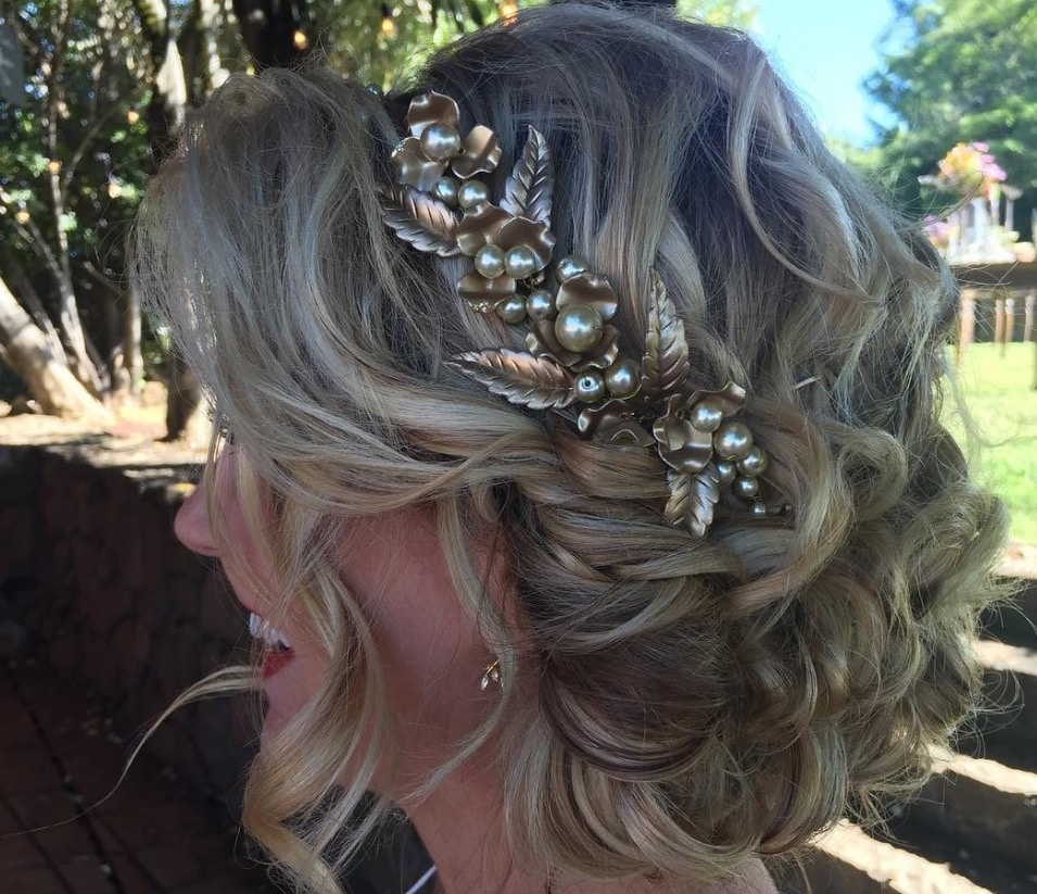 Disney hairstyles: Side view of a blonde woman with a curly updo and gold headband