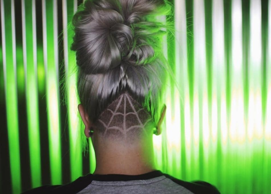 Back view of grey haired Instagramer with topknot and spiderweb undercut shaved