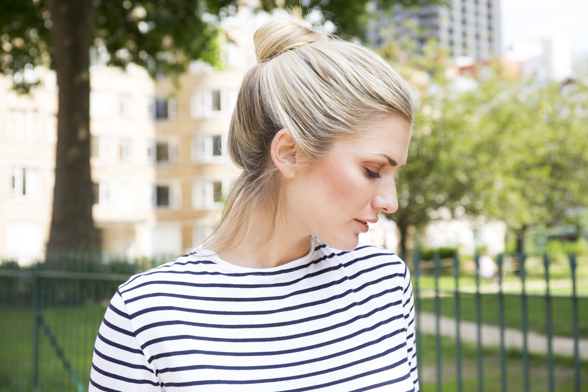 Easy updo - High bun on blonde model wearing a striped top in a park