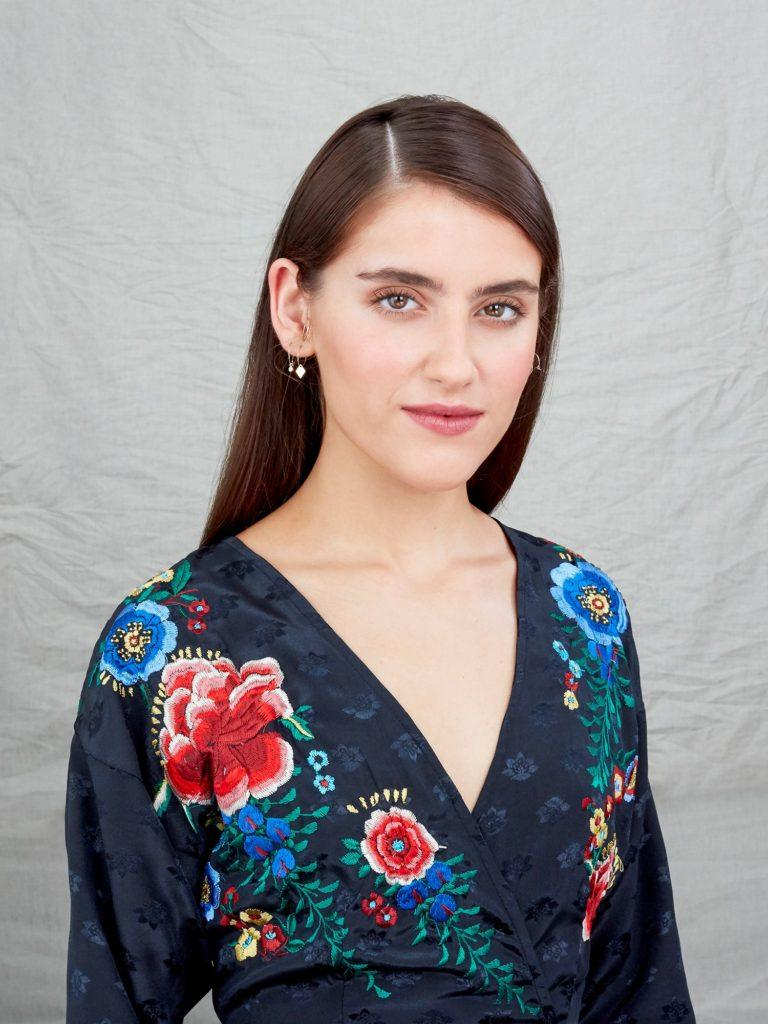 How to style long hair: Studio image of a brunette model with long straight hair styled in a sleek side parting, wearing a floral top