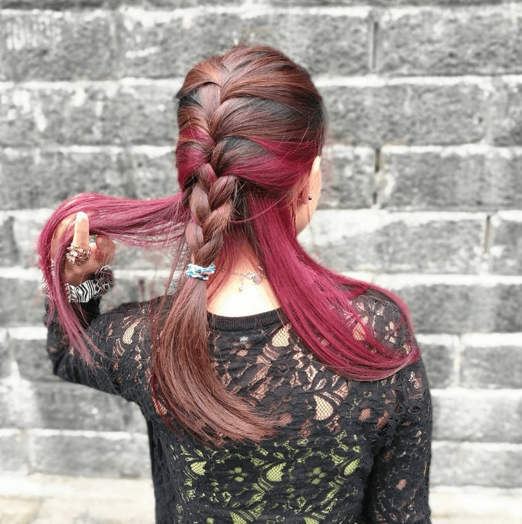 French braid styles: the back view of a young woman with a half-up French braid with brown and red hair