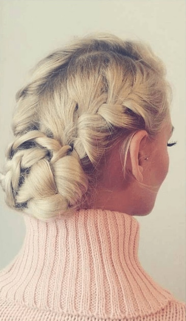 French braids hairstyles: back view of a blonde woman with French braided bun