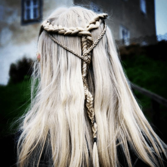Medieval hairstyles: Back view close-up of a woman with grey white hair in a half-up medieval braided style