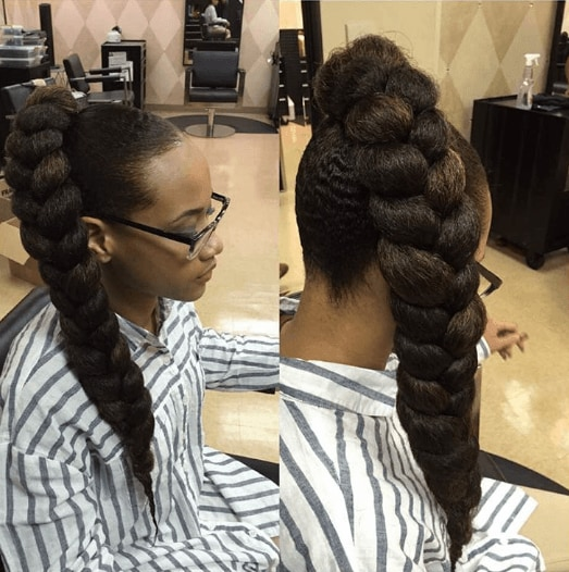 woman with long braided ponytail on dark brown hair sitting in hairdressers wearing striped shirt and reading glasses
