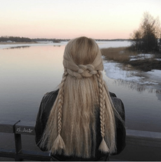 Medieval hairstyles: Back view of a woman with long blonde crimped hair in a half-up braid, looking out over a lake