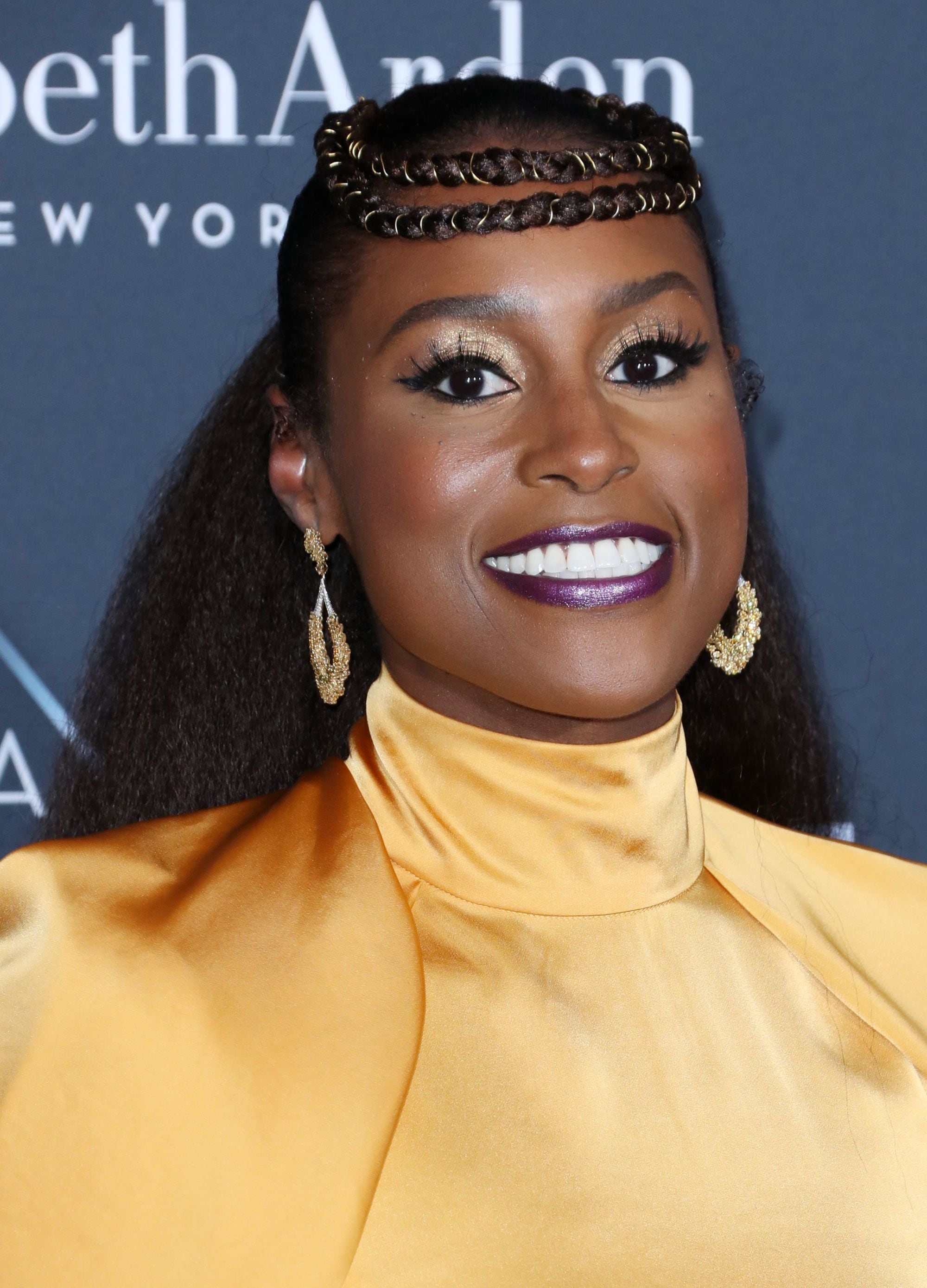 Black history month hairstyles: Close up shot of Issa Rae with a traditional African double Halo braids with a kinky low dark brown long ponytail, wearing a yellow dress on the red carpet