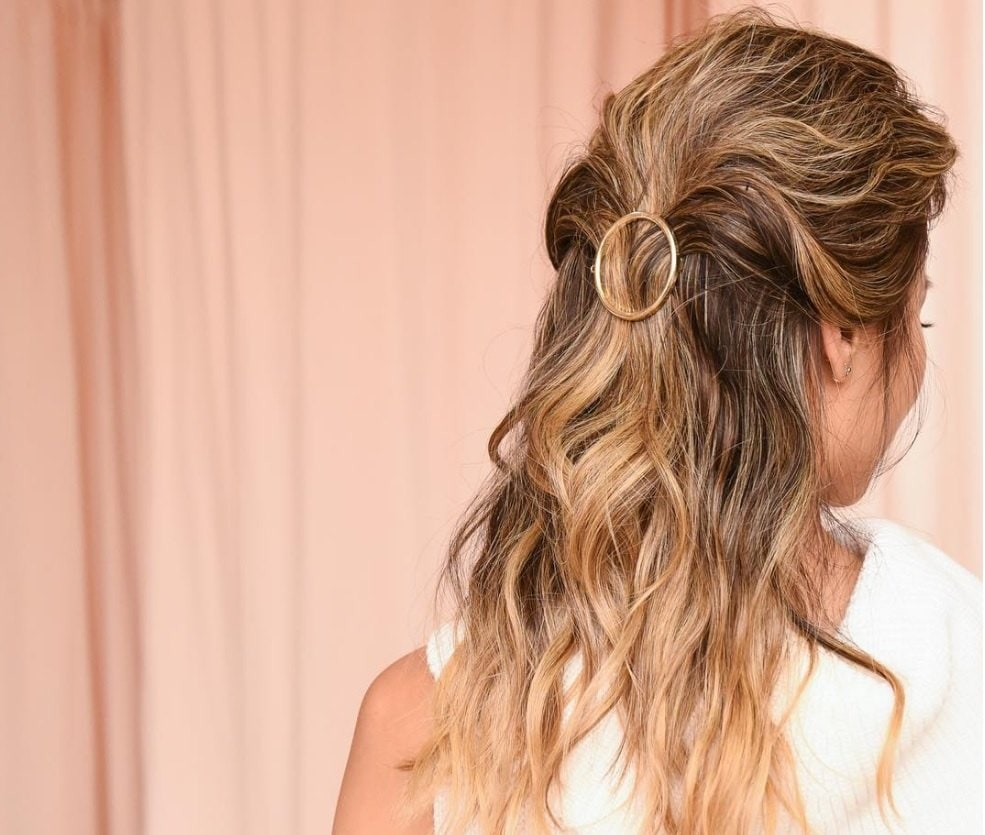 back view of Jamie Chung with blonde and brown highlighted hair fixed with a round accessory wearing a white dress