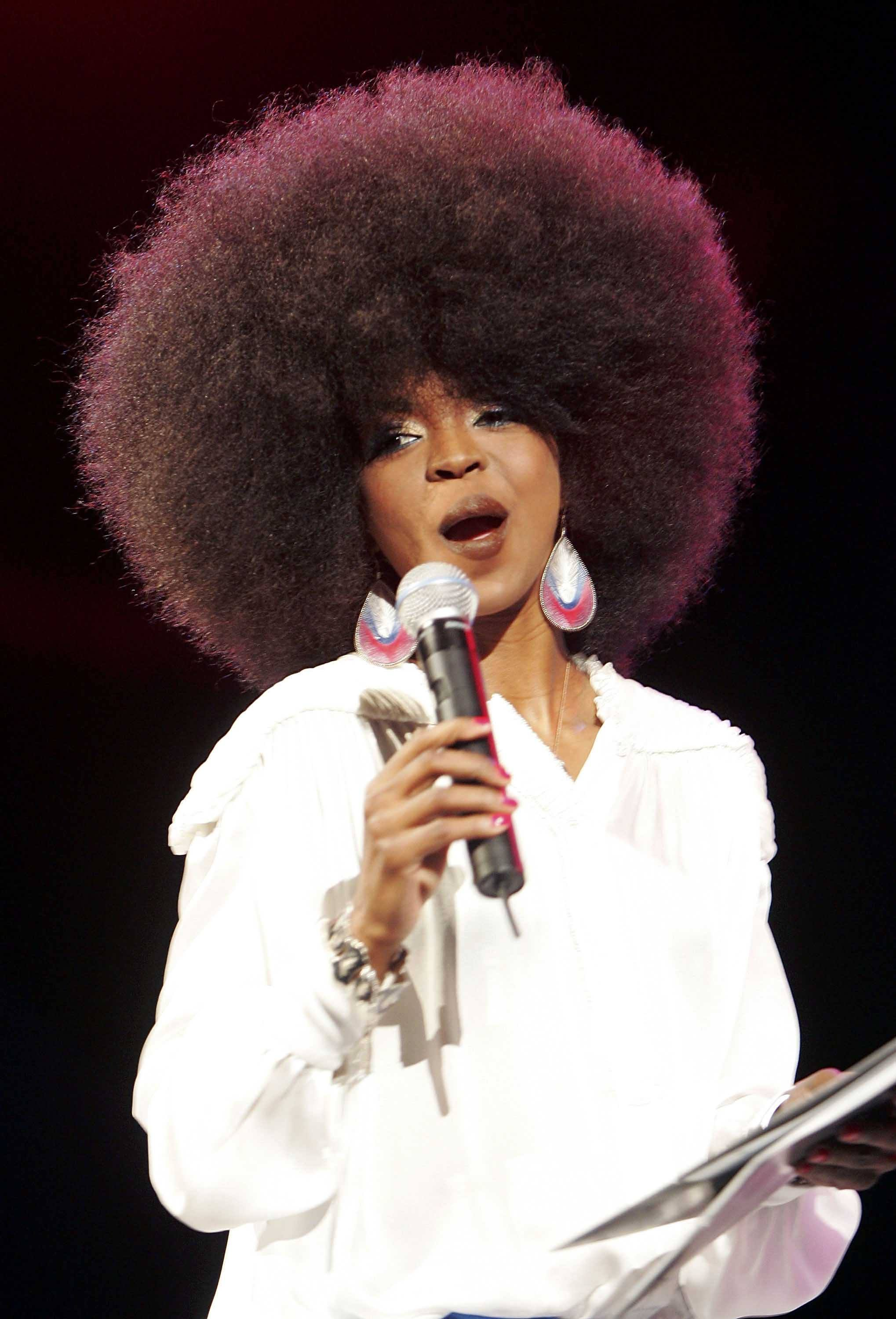 Black history month hairstyles: Close up shot of Lauryn Hill with a big afro, wearing big earrings and posing on the stage