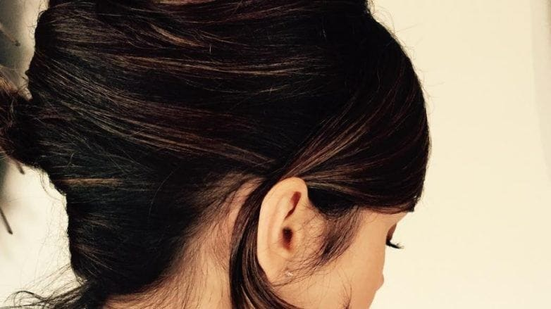 back view of actress Lily Collins with her dark brown hair worn in a french twist updo and one piece of hair tucked behind her ear