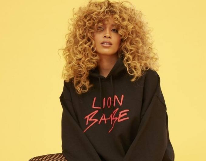 close up shot of lion babe with big blonde curly hair, wearing jumper in a studio