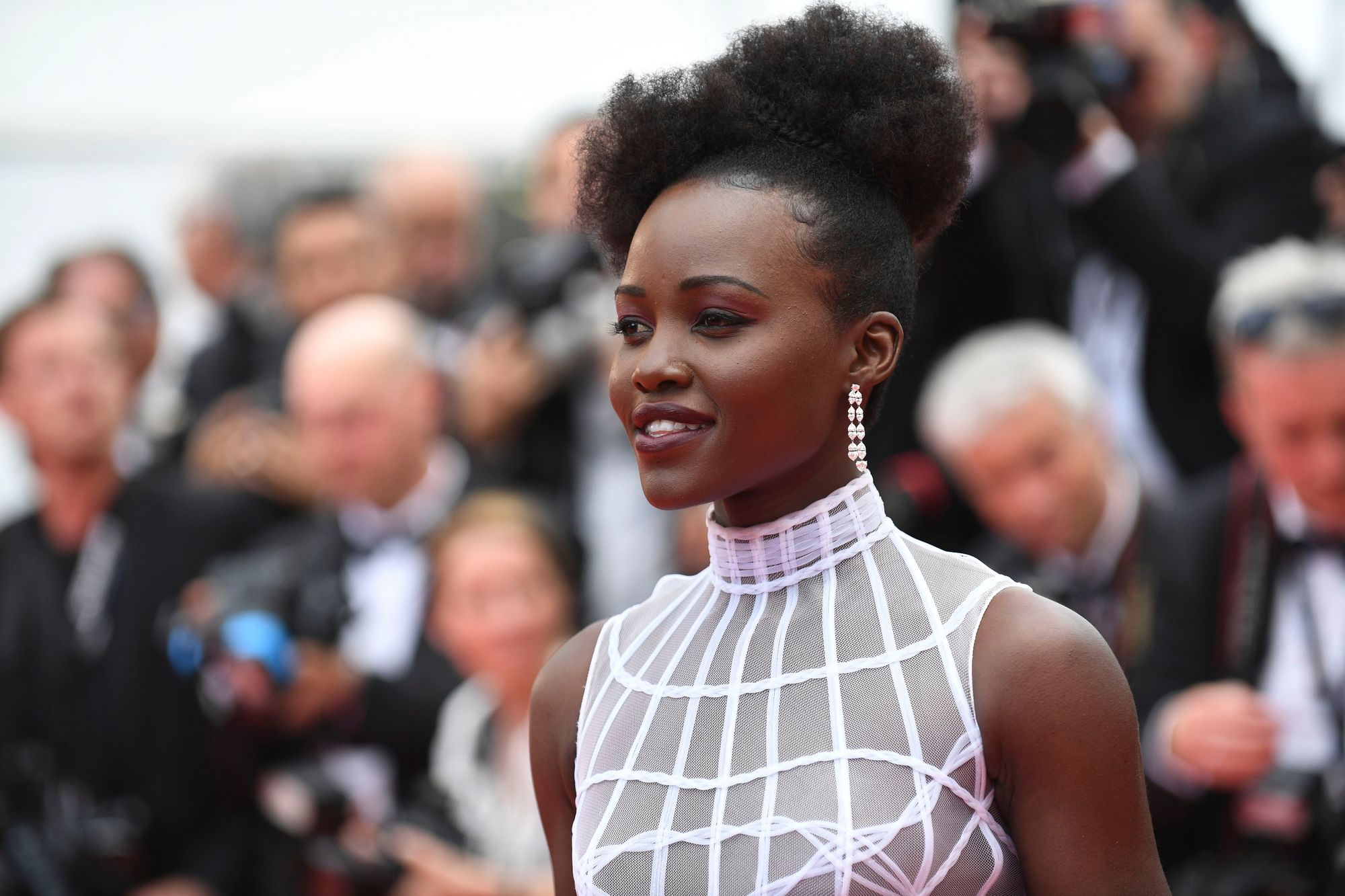 Black history month hairstyles: Close up shot of Lupita Nyong'o with an afro puff bun, with a puff quiff at the front, wearing white dress with drop pearl earrings