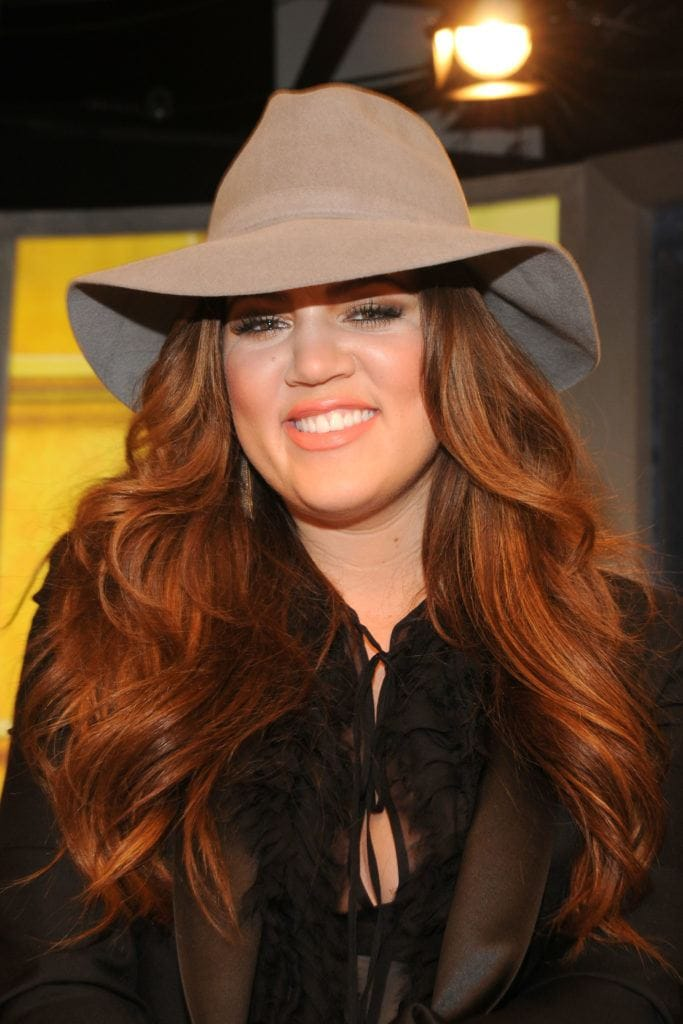 front view image of Khloe Kardashian wearing a beige hat with warm chesnut colour blonde brown hair