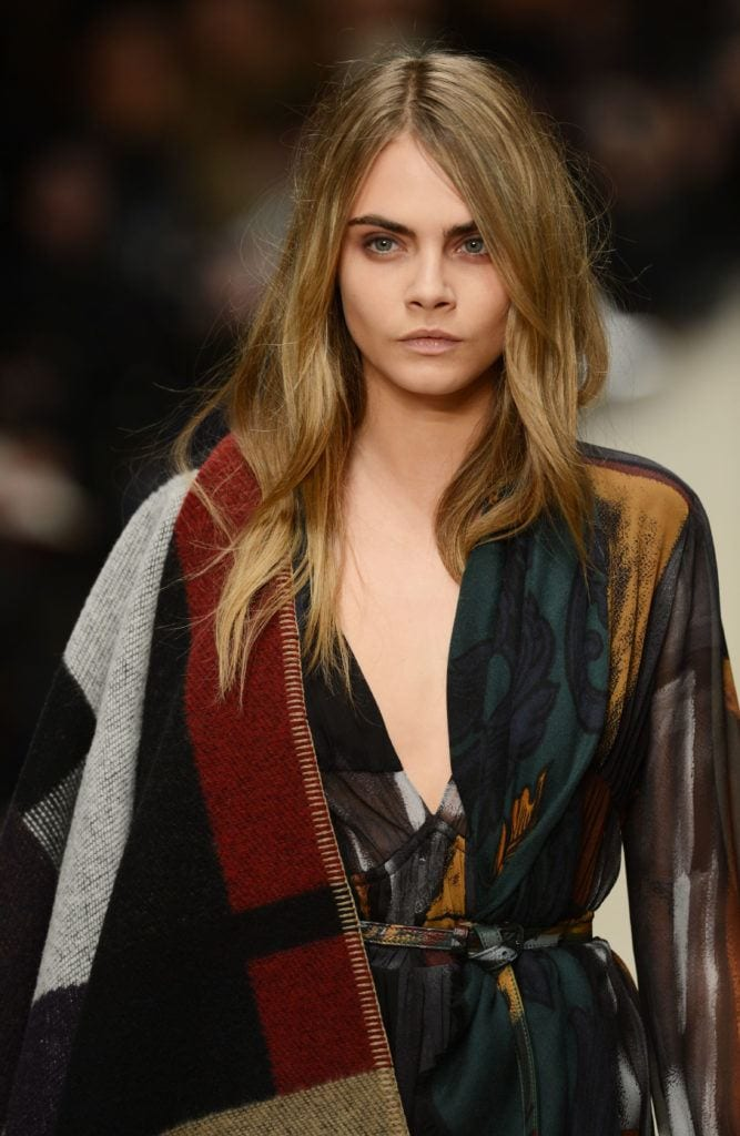 front view image of Cara Delevingne on the runway with blonde brown hair