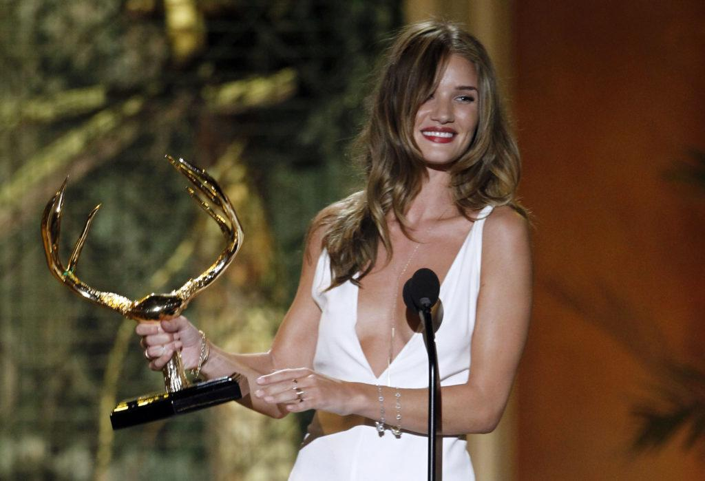 front view image of Rosie Huntington-Whitely holding an award, dressed in a white dress with long blonde brown hair