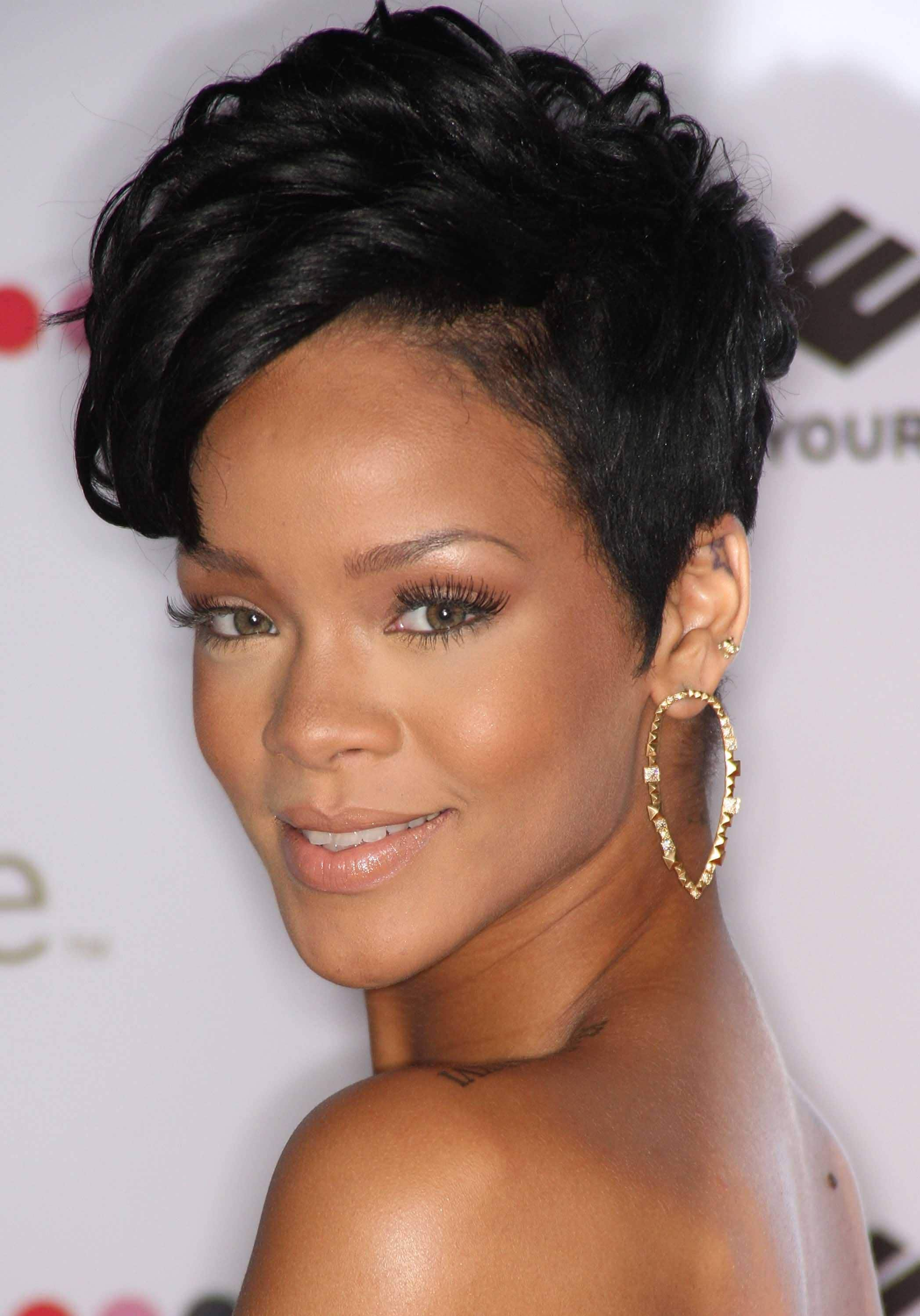 Black history month hairstyles: Close up shot of Rihanna with a dark brown wavy pixie with side-swept fringe, wearing golden hoop earring on the red carpet