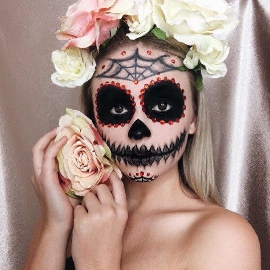 woman with sugar skull makeup and a pastel flower crown