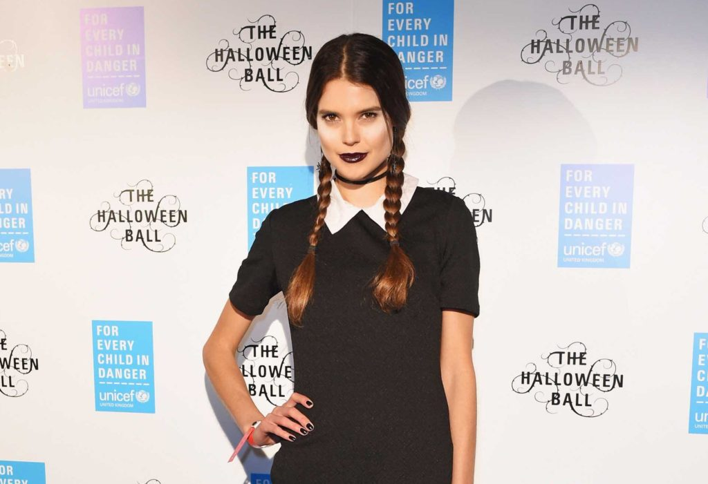 Sarah Ann Macklin on the red carpet with her dark brown hair styled into pigtail plaits and dressed like wednesday addams