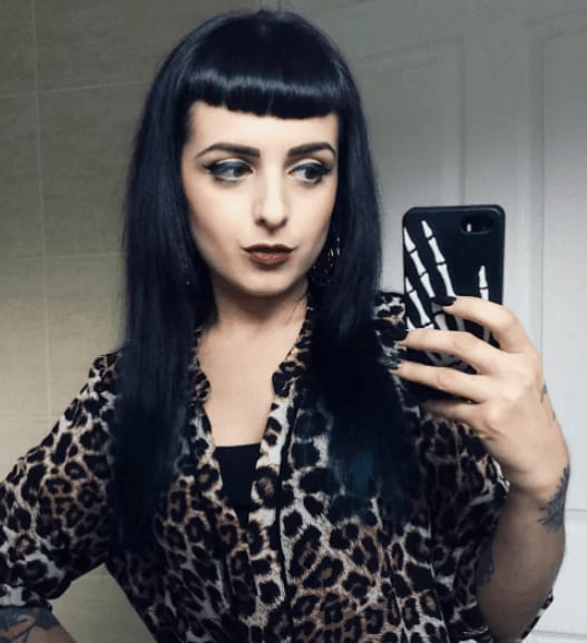Goth hairstyles: Front view of a women with long dark hair and a micro fringe