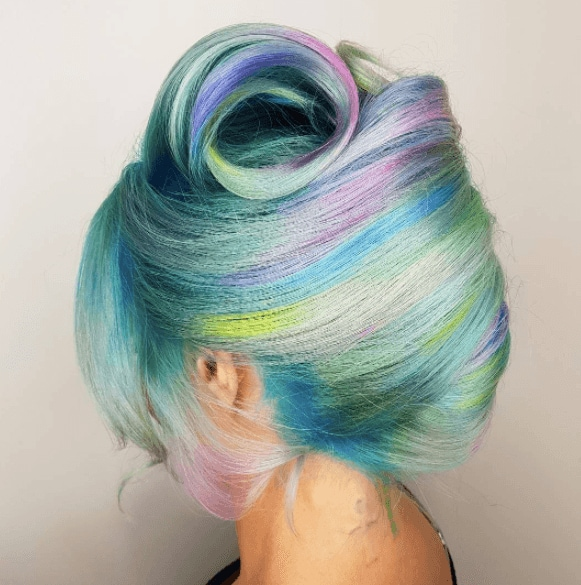 Unicorn hair: Woman's multicoloured pastel hair swept up into a french twist