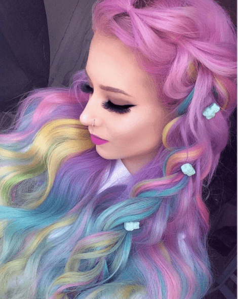 Unicorn hair: Front view of a woman's hair which has pink, yellow, blue and purple, worn in an oversized braid with loose waves
