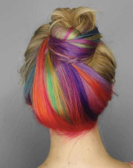 Unicorn hair: Back view of a woman with honey light brown hair worn in a bun with hidden rainbow red, green, yellow and purple highlights