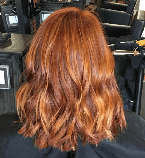 back view or woman's wavy copper coloured hair - red balayage