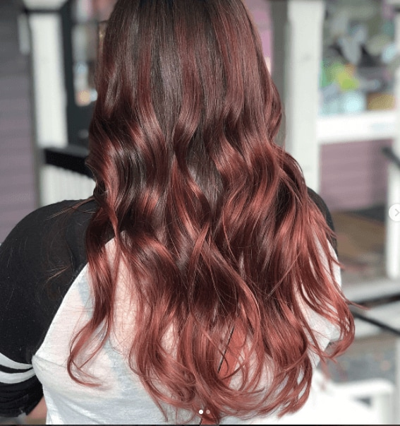 back view of a womans hair with long tumbling curls and red balayage