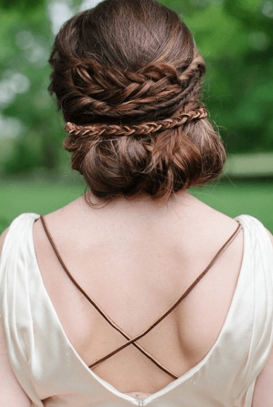 Medieval hairstyles: Back view of a woman's brunette hair with a braided rolled updo