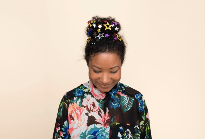 image of a woman with her hair in a top knot bun with glitter