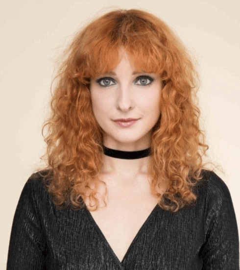 front facing image of a woman with red fluffy curls - going out hairstyles