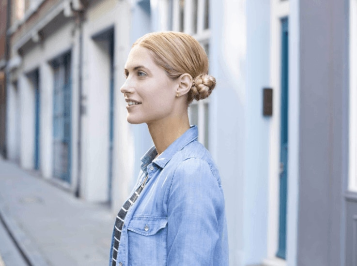 side view of a woman with blonde braided space buns