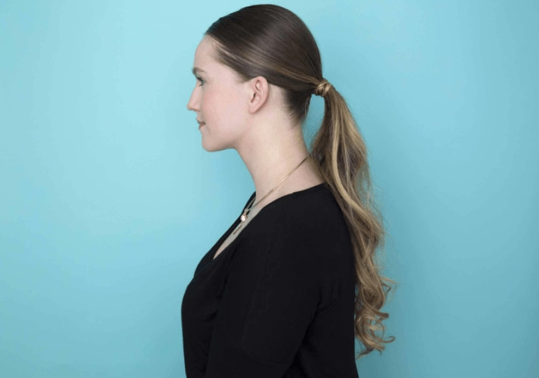 side view of a woman with long dark blonde hair in a low wavy ponytail
