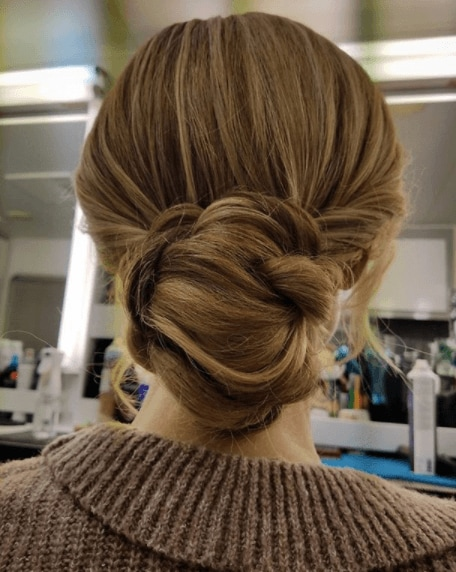 back view of a woman with her hair in a bun with dark honey blonde hair colour - blonde brown hair