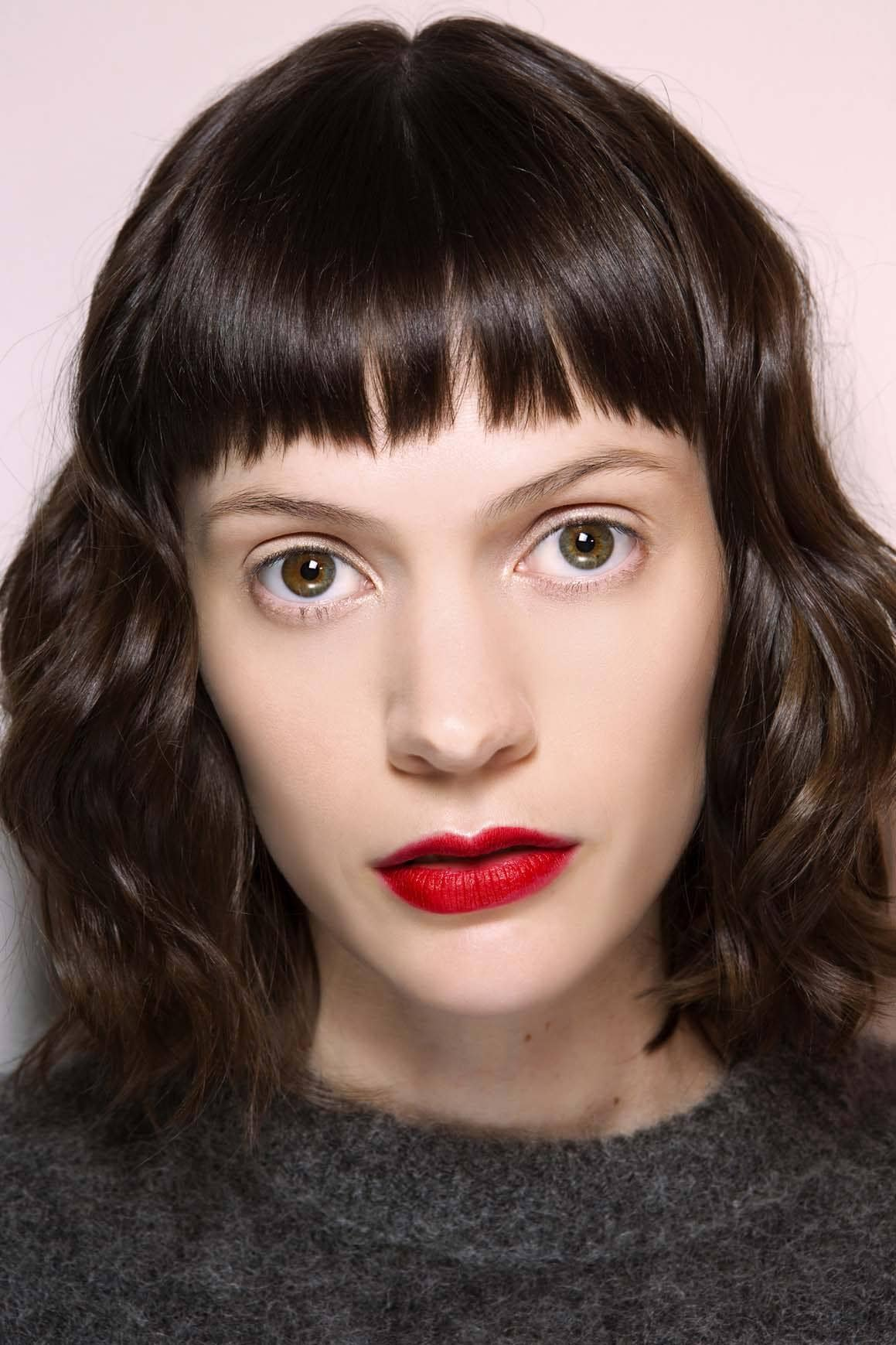 Short bangs: Woman with dark brown glossy wavy hair with micro fringe and red lipstick.
