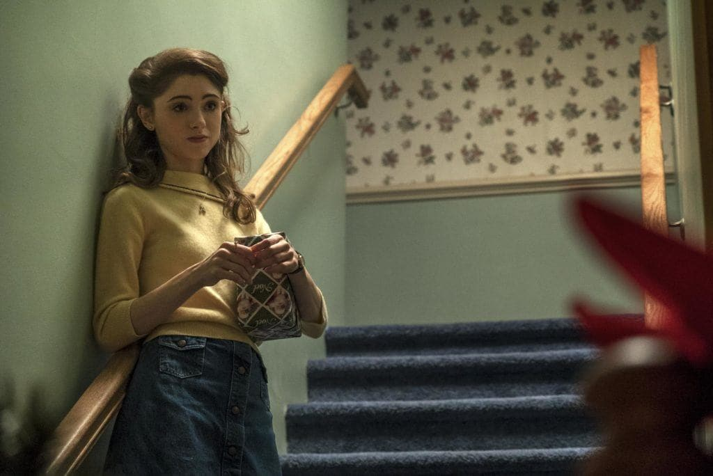 nancy from stranger things with her brunette hair pinned back into a half up look wearing a yellow top and blue jeans