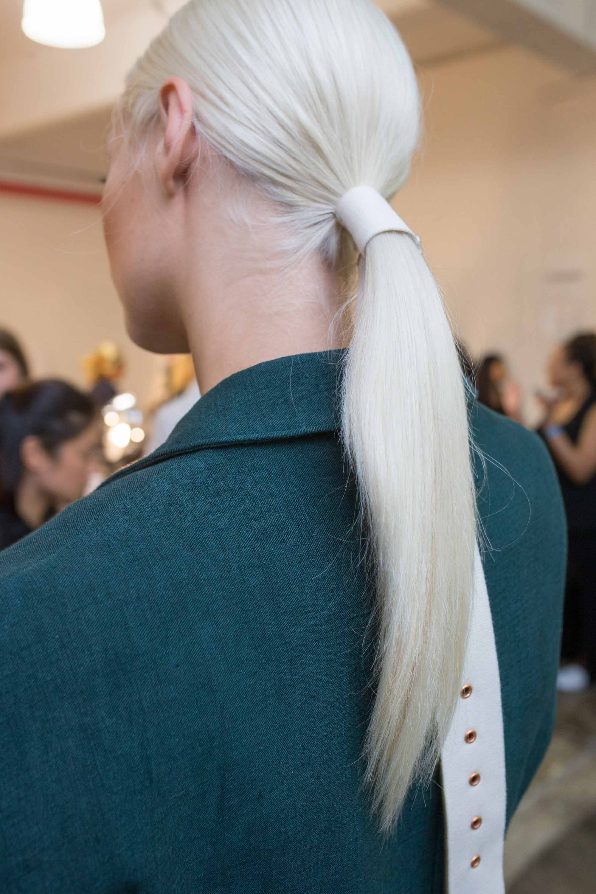 Easy updo - backstage with a model wearing a belted ponytail on platinum blonde hair